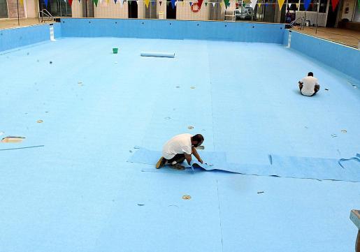 Los operarios instalaban el pasado miércoles la nueva lámina geotextil en la piscina grande.