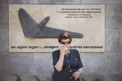Una mujer llora durante la ofrenda foral ante el memorial de los pasajeros que fallecieron en el accidente del vuelo JK5022 de Spanair, ocurrido en el aeropuerto de Barajas hace siete años.
