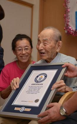 Yasutaro Koide junto al certificado que le certifica como el hombre más longevo del mundo atribuido por el libro Guinness de los Records.
