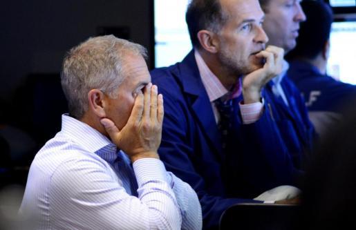 Trabajadores de la Bolsa de Nueva Yorl este lunes al final de la sesión. Las acciones globales reportaron una de sus mayores caídas desde los embates de la crisis financiera mundial en 2008.