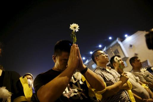 A man prays with a flower at a memorial service to pay tribute to victims of last week's explosions, near the 3-km (2-mile) exclusion zone, at the Binhai new district in Tianjin, China, August 18, 2015. China said on Tuesday it is investigating the head of its work safety regulator who for years allowed companies to operate without a license for dangerous chemicals, days after the blasts in a Tianjin port warehouse storing such material killed 114 people. REUTERS/Kim Kyung-Hoon TPX IMAGES OF THE DAY