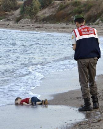Un policía turco trabaja junto al cuerpo sin vida de un niño refugiado ahogado, en la costa del pueblo de Bodrum.