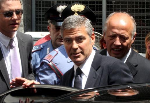 El actor estadounidense George Clooney (c) abandona el Tribunal Penal de Milán (Italia) tras ofrecer su testimonio en un juicio con tres imputados por la creación de una línea de moda no autorizada que llevaba su nombre.
