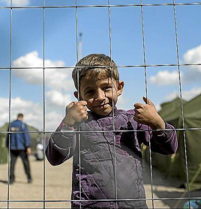 Un niño de Damasco se asoma por la verja del campo de refugiados de Roszke, en Hungría, punto de encuentro y salida hacia otros destinos europeos. l Pág. 11