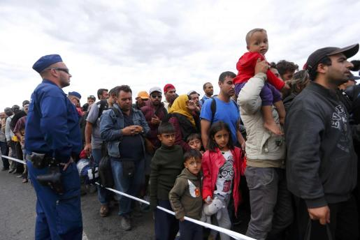 Un grupo de refugiados en Rozke (Hungría) pasando junto a un policía.