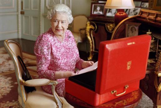 Fotografía cedida por Buckingham Palace de julio de 2015 de la reina Isabel II, sentada frente a una de las cajas rojas oficiales en las que usualmente recibe documentos importantes.