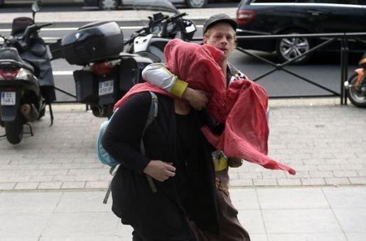 Christophe Champenois, padre del niño, tapa la cara de la madre, Charlène Cotte, a su llegada a los juzgados.