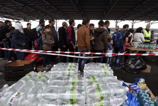Refugiados reciben comida de manos de voluntarios de la Cruz Roja en Nickelsdorf (Austria).