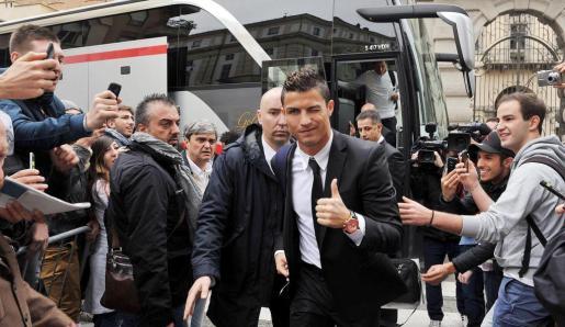 El delantero portugués del Real Madrid Cristiano Ronaldo (c) saluda a los fotógrafos a la llegada del equipo al hotel Golden Palace de Turín (Italia).