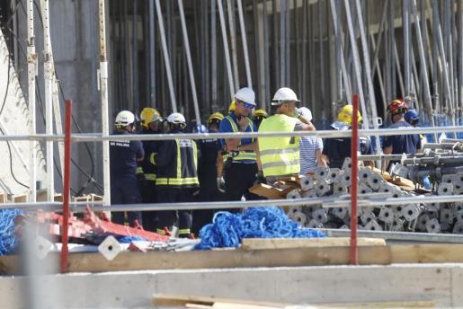 Operarios y bomberos inspeccionan las obras donde tuvo lugar el derrumbe.