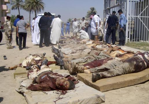 Varios iraquíes inspeccionan los cuerpos de algunas víctimas a las puertas de un depósito de cadáveres de Mahmudiya, al sur de Bagdad.