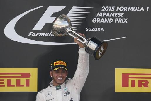 El británico Lewis Hamilton levanta el trofeo obtrenido en el Gran Premio de Japón.