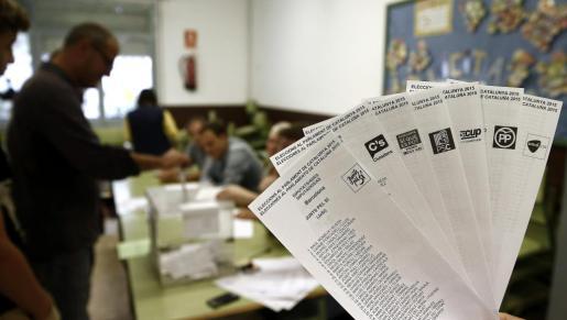 Una persona muestra las papeletas de los diferentes partidos que concurren a las elecciones al Parlamento Catalán.