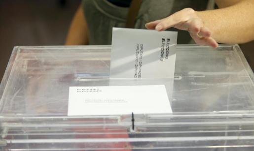 Una mujer deposita su voto en una urna en las elecciones catalanas.