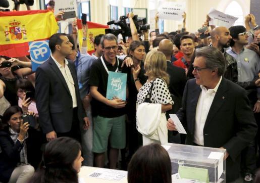 Artur Mas vota ante la presencia de banderas españolas.