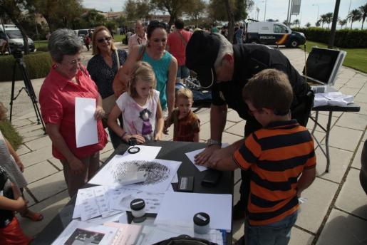 Un policía, enseñando a los niños a tomar las huellas dáctilares.