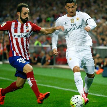 El delantero portugués del Real Madrid, Cristiano Ronaldo (d), intenta superar al defensa del At. de Madrid, Juanfran Torres.