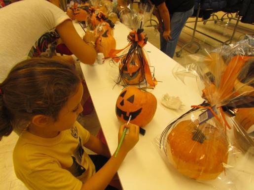 Una niña prepara su calabaza de Halloween.