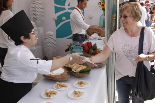 Una mujer se hace ocn uno de los platos de la Mostra de la Llampuga.