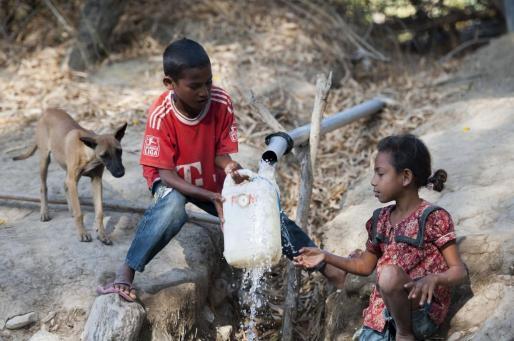 Un niño y una niña recogen agua en una garrafa en Malaka, Indonesia.