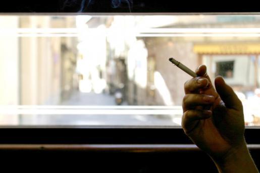 Un fumador con un cigarrillo en la mano.
