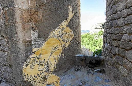 Una silueta en cartón de Lluís Salvador parece observar a través de las murallas de Dalt Vila. Foto: DANIEL ESPINOSA