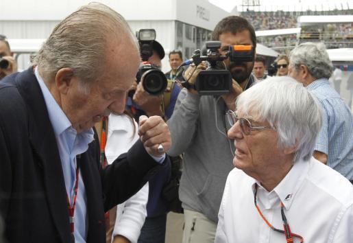 El rey Juan Carlos (i) conversa con el presidente y director ejecutivo de la Formula Uno, Bernie Ecclestone (d).