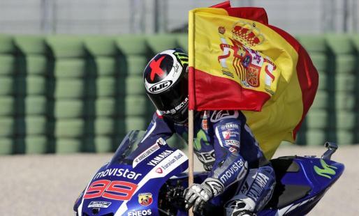 """Jorge Lorenzo porta una bandera de España tras ganar la carrera y el mundial de Moto GP en el circuito """"Ricardo Tormo"""" de Valencia."""