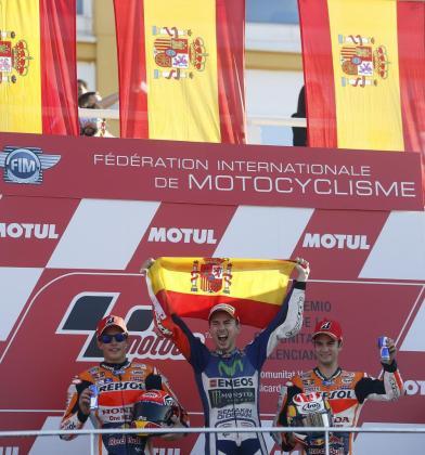 Jorge Lorenzo sostiene la bandera de España en el podio, junto a Marc Márquez y Dani Pedrosa.