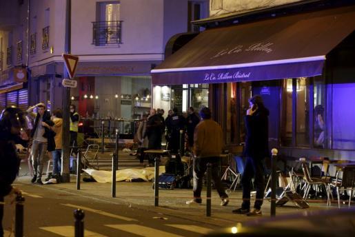 Varios cadáveres yacen frente a un restaurante.