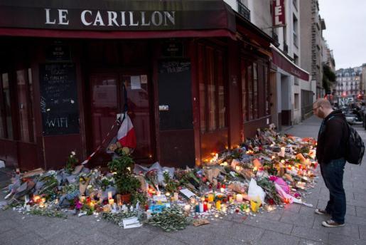 Un hombre permanece frente a las flores y velas colocadas en el resturante Carrillon en memoria a las víctimas de los atentados.