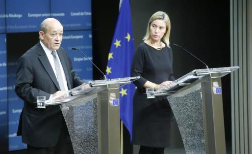 El ministro francés de Defensa, Jean Yves le Drian (izda), y la jefa de la diplomacia de la UE, Federica Mogherini (dcha), ofrecen una rueda de prensa este martes durante la reunión de ministros de Defensa de la Unión Europea en Bruselas.