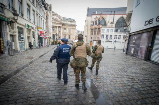 Un oficial de policía y dos soldados patrullan una calle de Bruselas.