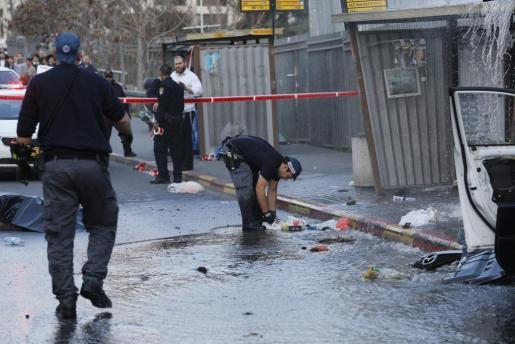 Miembros de la policía israelí inspeccionan el lugar donde un palestino fue abatido por la policía tras empotrar su coche contra una parada de autobús, en Jerusalén.