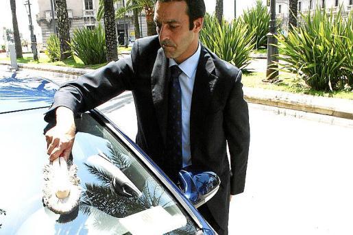 Foto de archivo de un chófer limpiando un coche oficial ante el Consolat.
