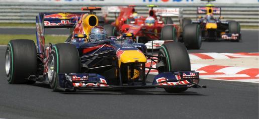 El piloto alemán de Fórmula Uno Sevastian Vettel de Red Bull (en primer plano) conduce su monoplaza seguido del español Fernando Alonso (centro)de Ferrari que acaba de adelantar al australiano Mark Webber de Red Bull (dcha) durante el Gran Premio de Hungría.