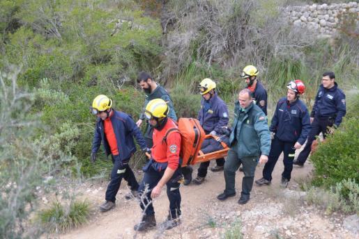 Imagen de los diferentes equipos de emergencias trasportando en camilla a la mujer herida hasta un coche policia.