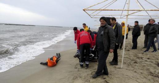Voluntarios y gendarmes retiran el cadáver de una mujer, ahogada tras naufragar la embarcación en la que trataba de llegar a Grecia desde la costa de Turquía, en la localidad costera de Ayvalik, en Balikesir (Turquía), este martes 5 de enero de 2016. Al menos 20 personas han muerto ahogadas tras naufragar las embarcaciones en las que trataban de llegar a Grecia desde la costa de Turquía, según informa el diario turco Hürriyet.