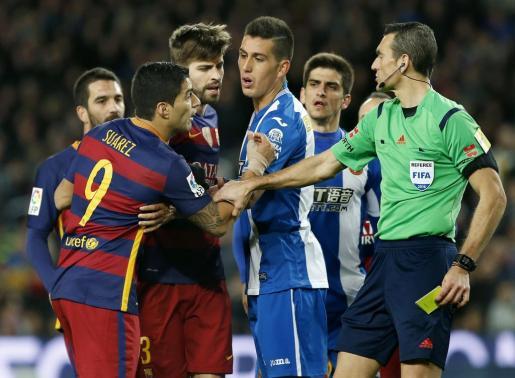 El árbitro Juan Martínez Munuera (d) muestra la tarjeta amarilla al delantero uruguayo del FC Barcelona Luis Suárez (i), durante el partido de ida de los octavos de final de la Copa del Rey de fúbol entre FC Barcelona y RCD Espanyol.