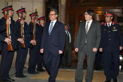 El nuevo presidente de la Generalitat, Carles Puigdemont (2d), y el expresidente Artur Mas, a su salida del pleno celebrado en el Parlament de Catalunya.