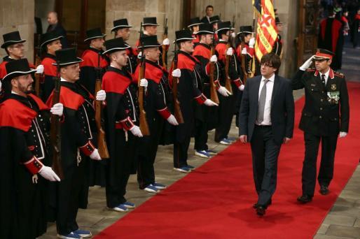 El presidente electo de la Generalitat, Carles Puigdemont, pasa revista a los Mossos d'Esquadra a su llegada al Palau de la Generalitat de Barcelona donde ha tomado posesión del cargo en relevo de Artur Mas.