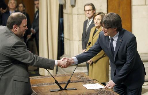 El vicepresidente de la Generalitat y conseller de Economía y Hacienda, Oriol Junqueras (i), estrecha la mano del presidente catalán, Carles Puigdemont, tras tomar posesión de su cargo.