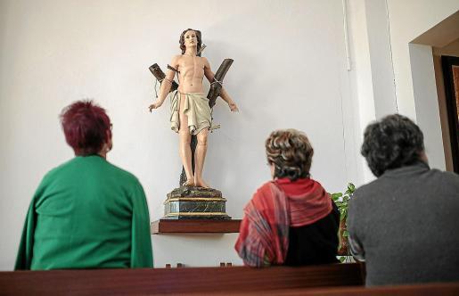 Vecinas de es Capdellà observan la talla de Sant Sebastià que salía en procesión.