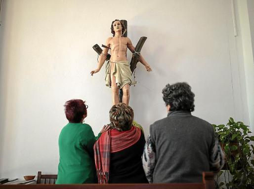 Tres vecinas de es Capdellà adoran la talla de Sant Sebastià que salía en procesión.
