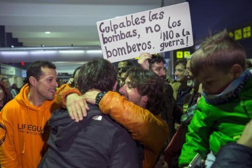 Los tres bomberos sevillanos, Julio Latorre, José Enrique Rodríguez y Manuel Blanco reciben una calurosa bienvenida por familiares y compañeros a su llegada a Sevilla.