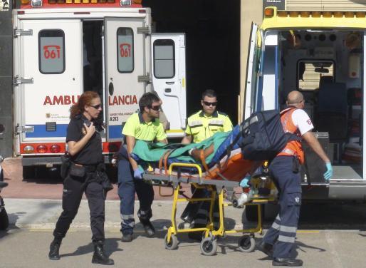 Los sanitarios, en el momento de la evacuación del herido en ambulancia.