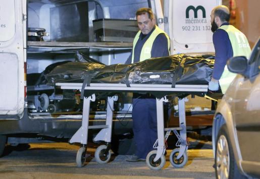 Funcionarios del retén fúnebre trasladan al furgón el cuerpo sin vida de una mujer de 73 años que ha muerto en Valencia acuchillada a manos supuestamente de su marido.