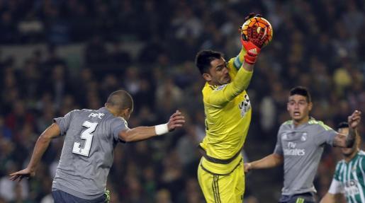"""El portero del Betis Antonio Adán (c) para el balón ante el defensa del Real Madrid Képler Laveran Lima """"Pepe"""" (i)."""