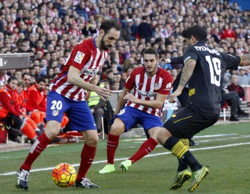 El defensa del Atlético de Madrid Juan Francisco Torres (i) con el balón ante el centrocampista argentino del Sevilla Éver Banega.