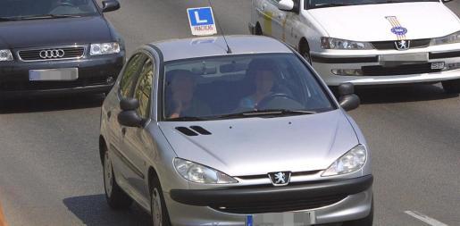 Un coche de autoescuela circula por la autopista.